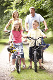 Family riding bikes in countryside. Looking cheerful Royalty Free Stock Images