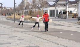 Family riding on roller skates Stock Images