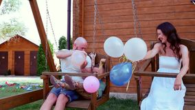 Family riding on a swing, portrait of a happy family, mom dad and son having fun, holding in his hand balloons, laughing stock video footage