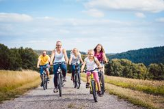 Family riding their bicycles on afternoon in the countryside royalty free stock photo