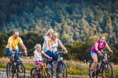 Family riding their bicycles on afternoon in the countryside stock image