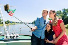 Family on river cruise with selfie stick in summer royalty free stock image