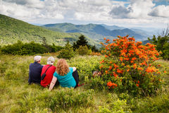 Family on Roan Mountain North Carolina. Family taking a rest off the Appalachian Trail through Engine Gap in the Roan Highlands near vivid orange flame azaleas stock photography
