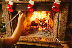 Family roasting marshmallows by the fire. Cozy chalet home  Royalty Free Stock Photography