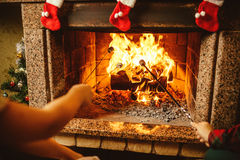 Family roasting marshmallows by the fire. Cozy chalet home  Stock Photo