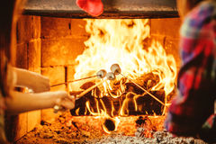 Family roasting marshmallows by the fire. Cozy chalet home with Stock Photos