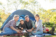 Family roasting marshmallows outside the tent Royalty Free Stock Photo