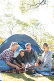 Family roasting marshmallows outside the tent Stock Images