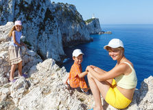 Family on Rocky cape. Family on rocky south cape of Lefkas island and lighthouse (Greece, Ionian Sea Stock Image