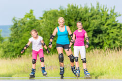 Family rollerblade with skates on country lane Stock Images