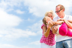 Family romping on field. With parents carrying child Stock Images
