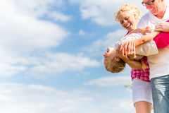 Family romping on field Stock Photos