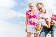 Family romping on field. With parents carrying child Royalty Free Stock Photography