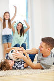 Family romping with soccer ball Stock Images