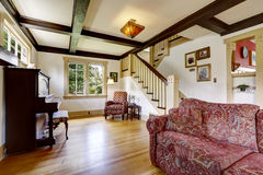 Family room with antique piano and comfortable red sofa Royalty Free Stock Photography