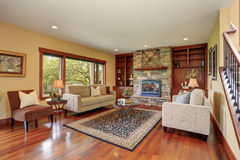 Family room in antique style with natural stone design fireplace and old sofa set. Stock Photos