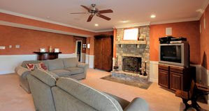 Family Room Interior. Wide angle view of a family room, with ceiling fan, couches, and fireplace. Horizontal format Royalty Free Stock Photo