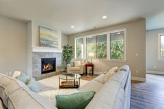 Family room interior features grey linen sectional. Lined with colorful pillows facing fireplace with grey tile surround across from glass top coffee table atop Royalty Free Stock Images