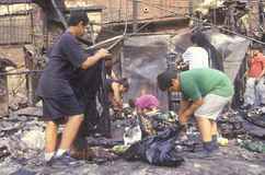 Family rummaging through home burned during riots, South Central Los Angeles, California Stock Images