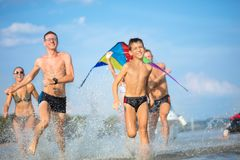 Family run a race in shallow sea water Stock Images