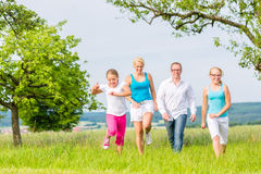 Family runing over field or lawn in summer Royalty Free Stock Photography