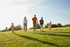 Family Running. Young Caucasian family running down a grassy hill together Stock Photo