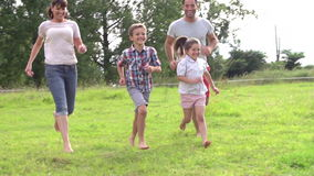 Family Running Across Field In Slow Motion stock video