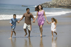 Family Running Along Beach Stock Photo