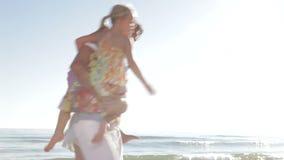 Family Running Along Beach Shoreline stock footage
