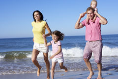 Family Running Along Beach Together Stock Photo