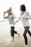 Family Running Along Beach Together Royalty Free Stock Photos