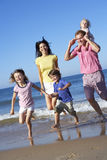 Family Running Along Beach Together Stock Image