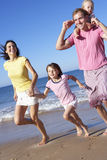 Family Running Along Beach Together Stock Photos