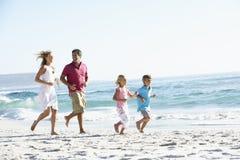 Family Running Along Sandy Beach Stock Image