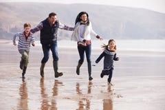 Family Running Along Winter Beach Royalty Free Stock Photos