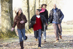 Family Running Through Autumn Countryside Stock Image