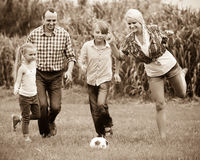 Family running with ball Royalty Free Stock Image