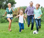 Family running with ball. Children and parents running with ball at sunny day Stock Photos