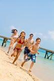 Family running on the beach stock image