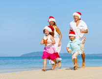 Family running on the beach in Christmas Royalty Free Stock Photos