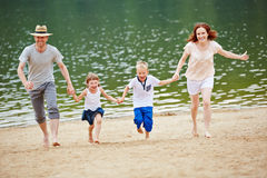 Family running on beach on summer Royalty Free Stock Photo