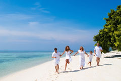 Family running on a beautiful tropical beach. Family of five celebrating a wedding anniversary running on a beautiful tropical beach stock photography