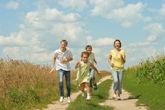 Family running on a dirt road. Happy family running on a dirt road stock photo