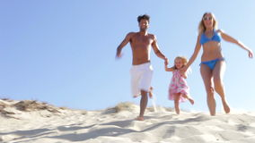 Family Running Down Sand Dune Together Stock Photo