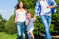 Family running fast in grass on meadow stock images
