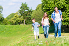 Family running fast in grass on meadow royalty free stock photography