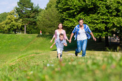 Family running fast in grass on meadow royalty free stock image