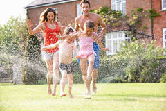 Family Running Through Garden Sprinkler Stock Image