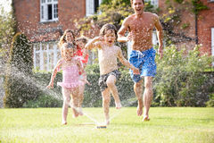 Family Running Through Garden Sprinkler Stock Images