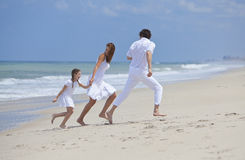 Family Running and Having Fun At the Beach Stock Images